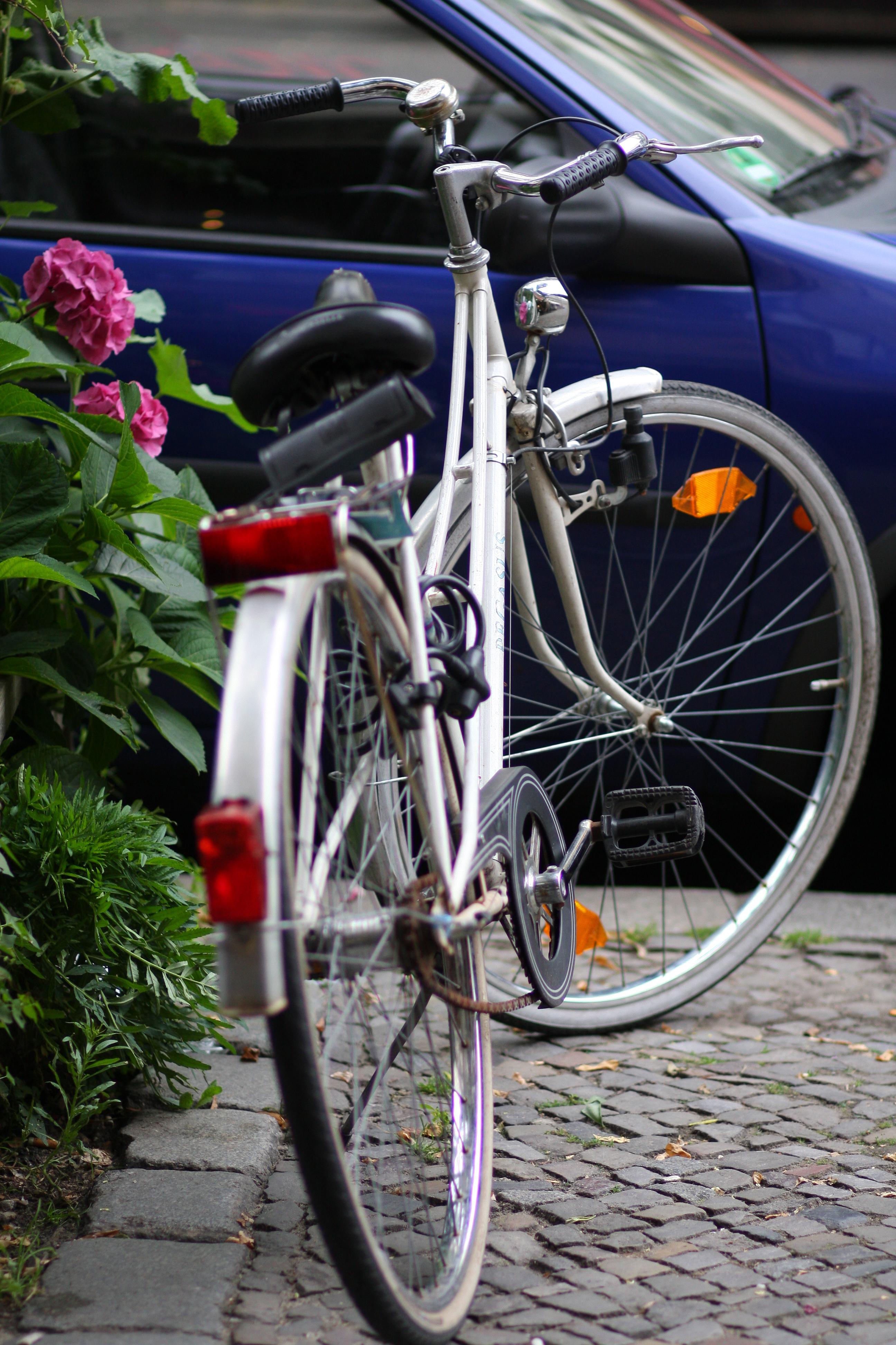 Vit cykel och blå bil